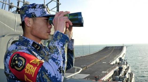 A naval soldier of the Chinese People's Liberation Army (PLA) views through a pair of binoculars onboard China's first aircraft carrier Liaoning as it visits a military harbour on the South China Sea in Sanya, Hainan province/AFP