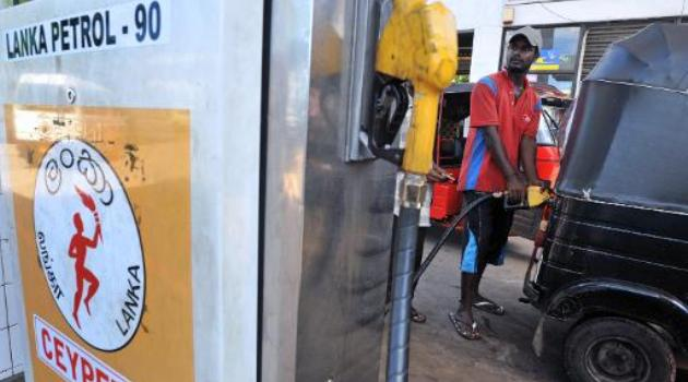 A Sri Lankan petrol pump attendant fills up the tank of an auto-rickshaw at a station in Colombo on May 25, 2008/AFP