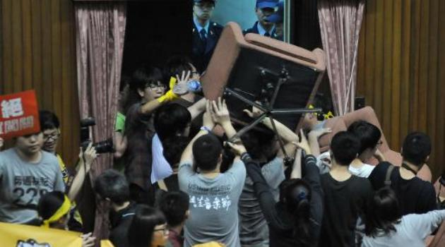 Protesters from anti-China activist groups use chairs to block the entrance to the Taiwanese Parliament as it prepares to pass trade and services agreements with China during a parliamentary session, in Taipei, on March 18, 2014/AFP