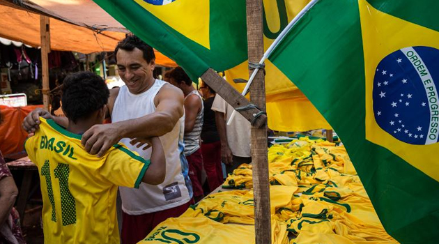 A boy tries on a Brazilian T-shirt on sale ahead of the FIFA World Cup 2014, in Mare shantytown (favela) in Rio de Janeiro, Brazil, on June 7, 2014/AFP