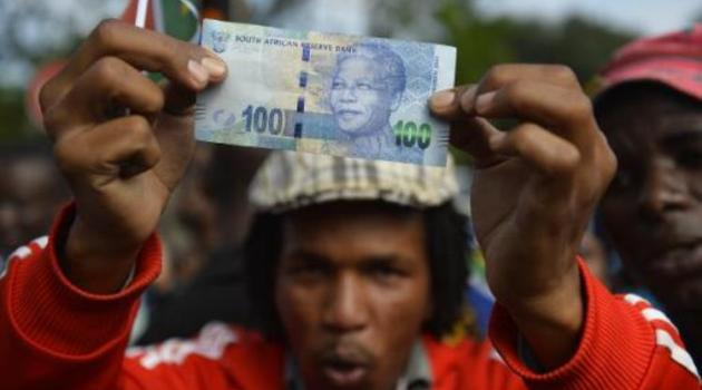 A man holds a 100 rand bill bearing the portrait of South African former president Nelson MandelaMandela as Mandela's funeral cortege drives through the streets in Pretoria on December 11, 2013/AFP