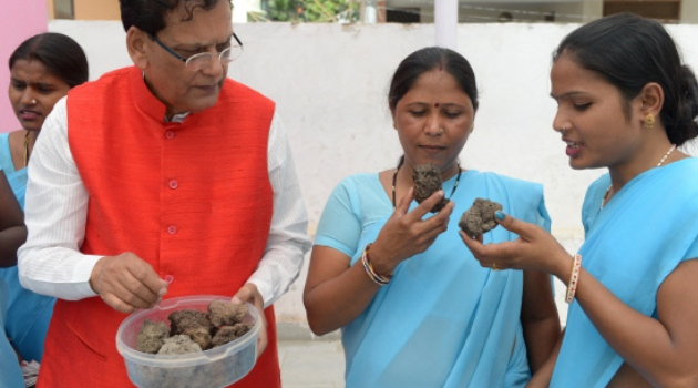 In this photograph taken on September 22, 2014, the founder of the Indian sanitation charity Sulabh International Bindeshwar Pathak (L) shows compost prepared from human excreta to former manual scavengers at the charity's campus in New Delhi/AFP