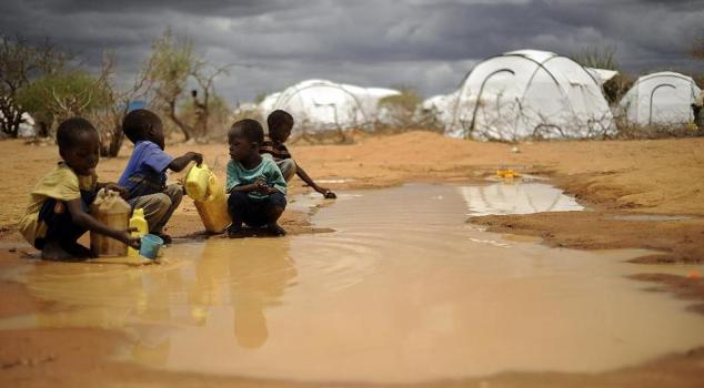 Children fetch water from a pond in the sprawling Dadaab refugee camp in Kenya. Food rations for refugees in Kenya are to be cut by half due to a shortage of funds, the United Nations says/AFP