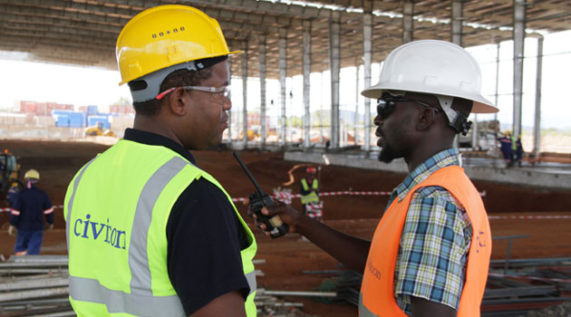 Civicon Site Engineer Gaddafi Odhiambo (right) and Trancentury Group CEO Dr Gachao Kiuna reviewing the ongoing construction works at the GZ Industries Aluminium Cans Factory near Emali/CFM BUSINESS