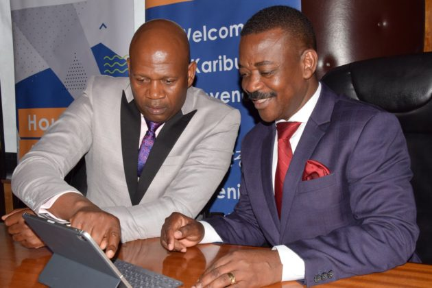 Shelter Afrique Managing Director Andrew Chimphondah explains financials results to Shelter Afrique Chairman Nghidinua Daniel when the Company released its 2019 half year result last month. e1570606346546 - Kenya played key role in Shelter Afrique turnaround to profitability