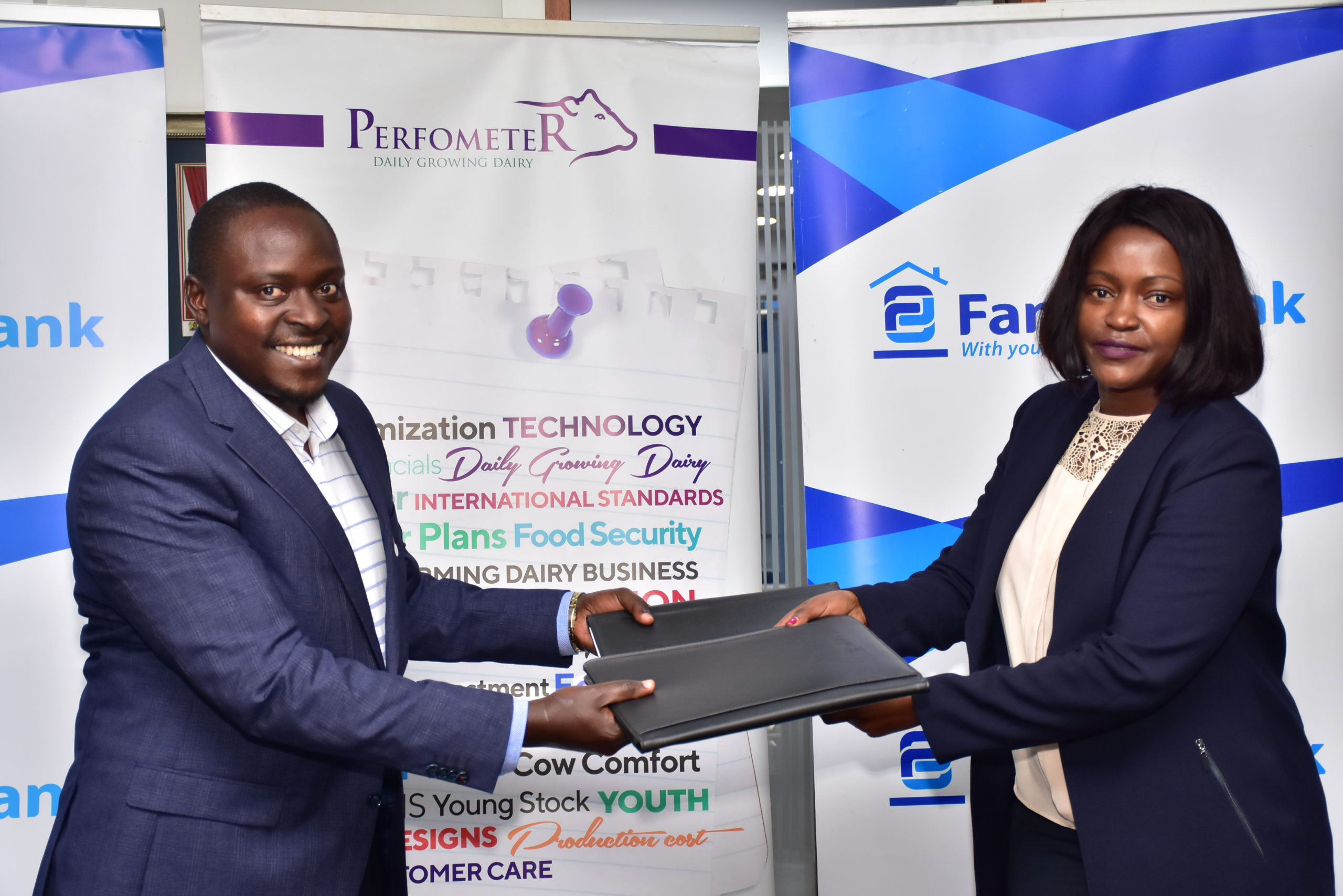 Performeter Head of Business David Maina (L) and Family Bank CEO Rebecca Mbithi (R) after the signing of an agreement that will see 100,000 dairy farmers boost milk yield