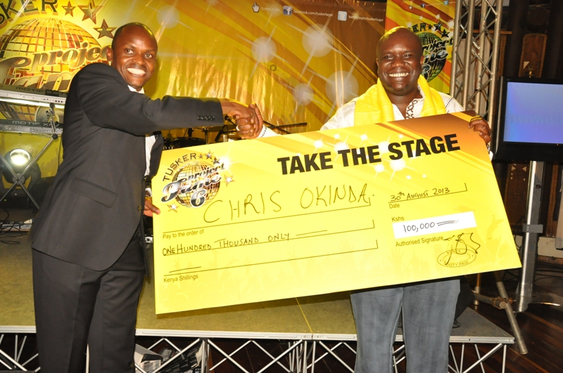 The winner of the Tusker Project Fame Media Ignition receiving his cheque from Antony Esyalai, Marketing Manager-Tusker.