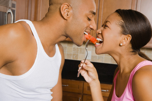 African American couple eating piece of fruit