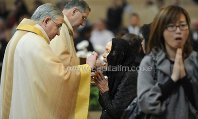 Archbishop Jose Gomez (L), and retiring Cardinal Roger Mahony give communion/AFP