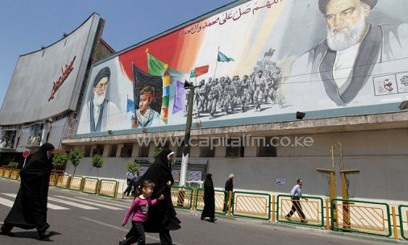 ranian women walk past a mural depicting Iran's supreme leader Ayatollah Ali Khamenei/AFP
