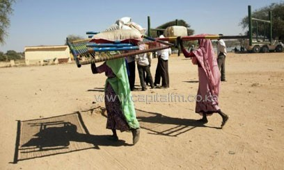 A handout from the United Nations-African Union Mission in Darfur (UNAMID) shows displaced women carrying their belongings in El Sireaf, in the state of North Darfur, on January 14, 2013/AFP