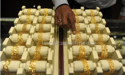 An Indian sales assistant arranges gold bangles for display in a jewellery shop in Hyderabad on May 13, 2013/AFP