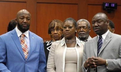 Tracy Martin (L) and Sybrina Fulton join the family's legal counsel Benjamin Crump on June 24, 2013, in Sanford, Florida/AFP