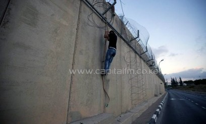 A Palestinian uses a rope to climb over a section of Israel's controversial concrete barrier that separates the West Bank from Jerusalem on August 12, 2013, in Beit Hanina/AFP