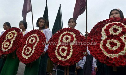 """Students hold wreaths with the number eight, during a march to mark the 25th anniversary of the democratic uprising, also known also as """"8888"""", in Yangon on August 8, 2013/AFP"""