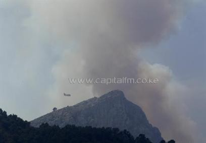 A plane from the fire brigade flies past smoke billowing from the mountains, near the village of Estellencs, on the island of Mallorca during a wildfire on July 28, 2013/AFP