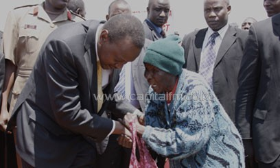 President Uhuru Kenyatta listens to an elderly woman who lives in an  IDP camp during the launch of the cash payment program/PSCU