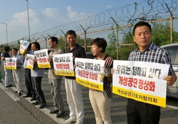 South Korean Kaesong-based workers hold placards reading 'We would like to work' in Paju near Kaesong in South Korea on August 14, 2013/AFP