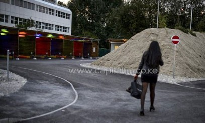 "A prostitute walks past so-called ""sex boxes"" at Switzerland's first sex drive-in on August 26, 2013 in Zurich/AFP"