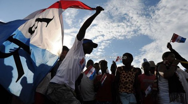 A man holds a party flag as supporters of the ruling Rwandan Patriotic Front (RPF) rally in Kigali on September 14, 2013/AFP