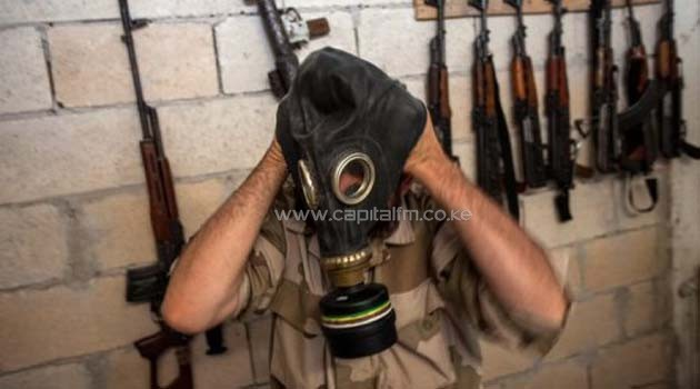 A Syrian rebel tries on a gas mask seized from an arms depot in the northwestern province of Idlib, on July 18, 2013/AFP