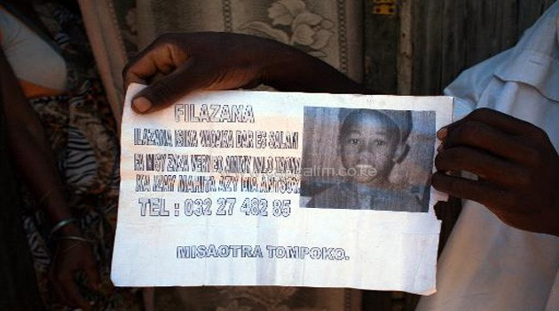 A person holds on October 4, 2013 a leaflet with a photo of Nomena, an 8-year-old boy found dead in Helleville at Nosy Be/AFP