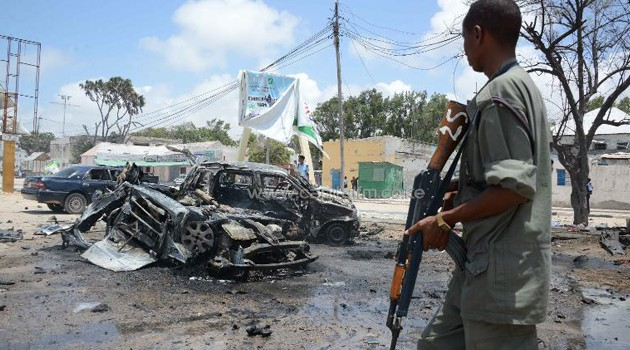 Armed man stands guard at the scene of two explosions in Mogadishu/AFP