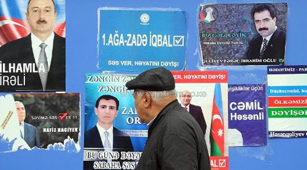 A man walks past a board plastered with campaign posters of presidential contenders in Baku, the capital of Azerbaijan, on October 7, 2013/AFP