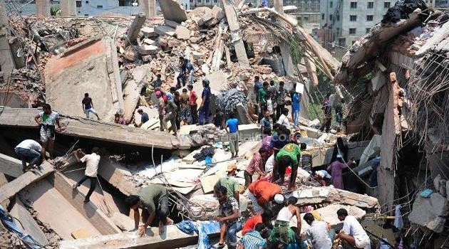 Rescue workers dig through the 2rubble of a collapsed garment factory in Bangladesh, on April 24, 2013/AFP