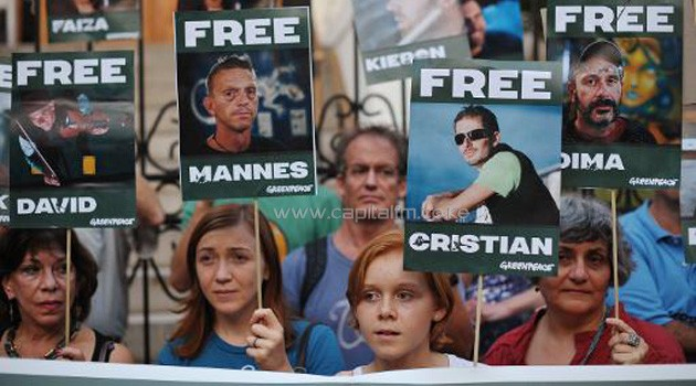 Demonstrators take part in a vigil outside of the Russian Center for Science & Culture on October 5, 2013 in Washington, DC to protest against the arrest of Greenpeace environmentalists and journalists by Russia/AFP