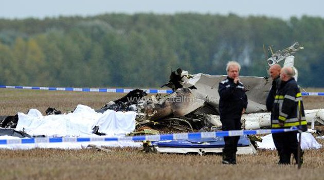 Belgian firefighters inspect pieces of debris at a site where a plane carrying 10 parachutists crashed/AFP