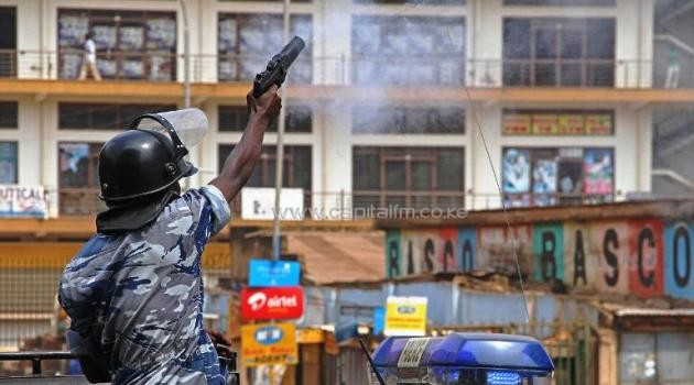 A police officer aims at opposition supporters protesting in Kampala on June 20, 2013/AFP