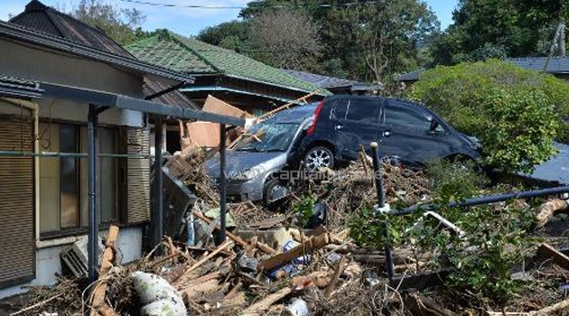 Damaged houses and vehicles are seen after a landslide caused by heavy rain bought by typhoon Wipha on Oshima island, on October 17, 2013/AFP