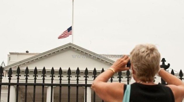 A woman takes a picture as the flag flies at half-mast at the White House/AFP
