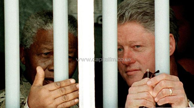 Bill Clinton and Nelson Mandela look out the jail cell window on March 27, 1998, where Mandela spent 18 of his 27 years as a political prisioner on Robben Island/AFP