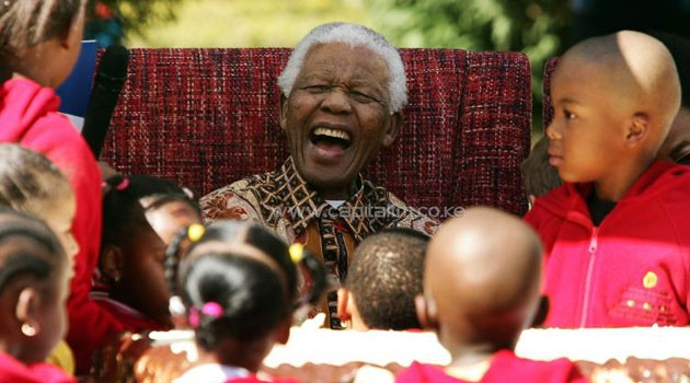 A file photo taken on July 24, 2007 shows former South African President Nelson Mandela joking with youngsters as they celebrate his 89th birthday/AFP