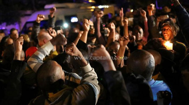 South Africans react as they pay tribute to Nelson Mandela following his death in Johannesburg on December 5, 2013/AFP