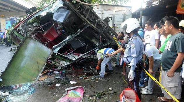 A policeman collects passengers' belongings after a bus fell from a highway, landing on a van and killing 22 people, in Manila on December 16, 2013/AFP