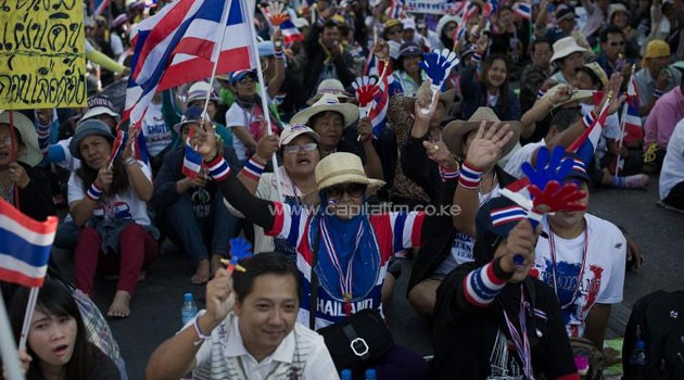 A Thai anti-government protesters wave national flags outside the customs department during ongoing rallies in Bangkok on January 14, 2014/AFP