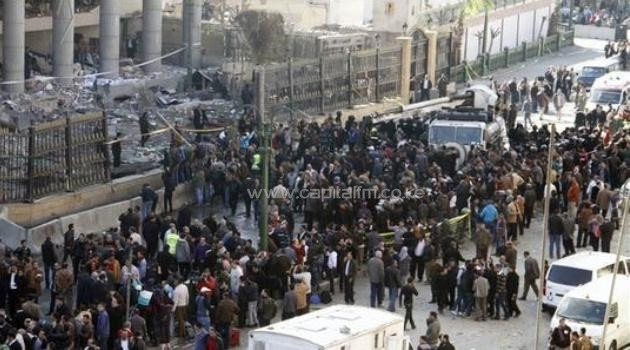 Egyptian emergency personnel and civilians gather at the site of a car bomb explosion outside the Cairo police headquarters in the Egyptian capital on January 24, 2014/AFP
