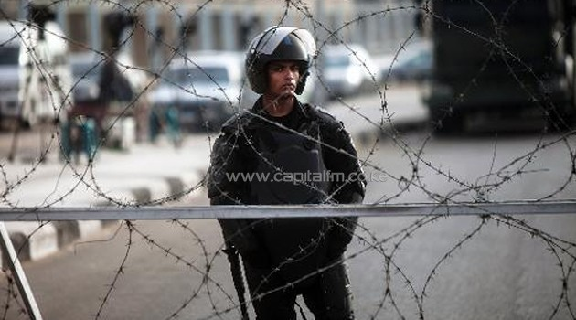 An Egyptian riot policeman stands guard behind barbed wire outside the Police Academy in Cairo on February 1, 2014/AFP