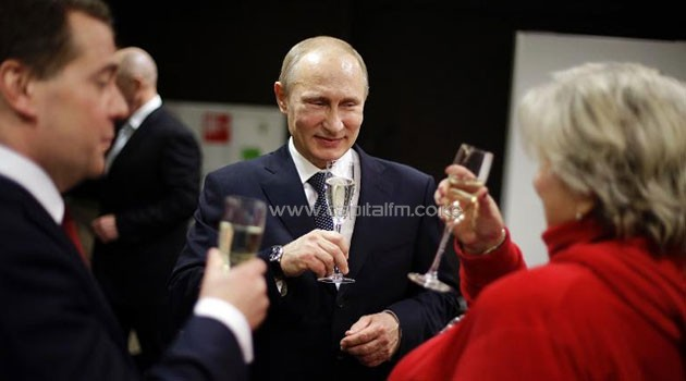 Russian President Vladimir Putin (C) toasts a glass of champagne with Prime Minister Dmitry Medvedev (L) and figure skating coach Tatiana Tarasova (R) in the presidential lounge at the Fisht Olympic Stadium on Feb 23. Photo/ AFP