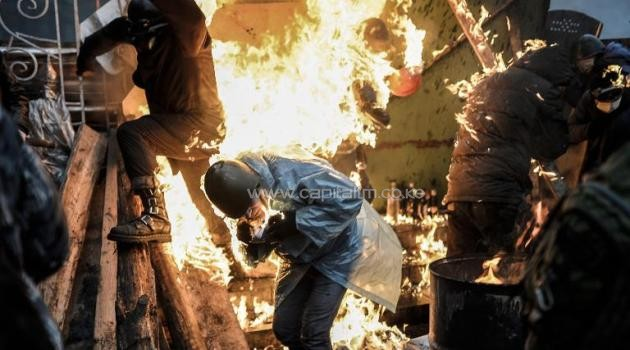 Ukrainian protesters burn as they stand behind a flaming barricade during clashes with riot police in Kiev, on February 20, 2014/AFP