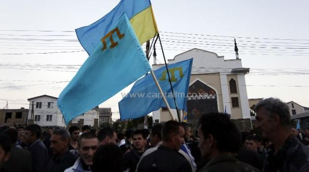 Crimean Tatars hold a Ukrainian and Tatar flags as they attend a memorial ceremony marking the 70th anniversary of the deportation of Tatars from Crimea, in Simferopol on May 17, 2014 /AFP