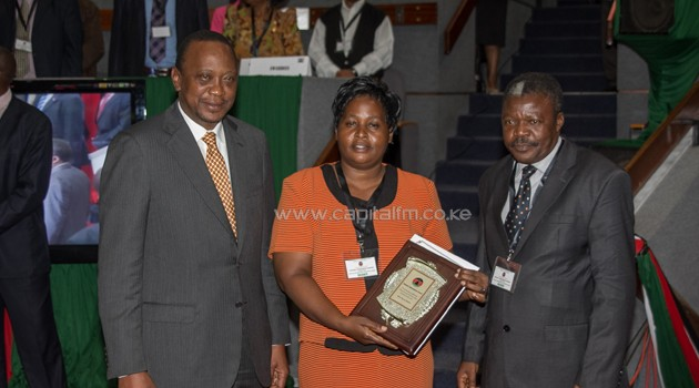 President Uhuru Kenyatta with the overall winner in the individual category, Mrs. Hellen Nechesa Machuka, Principal, Kombeni Girls' Secondary School, and her area Member of Parliament during the inaugural Huduma Ombudsman Awards Ceremony, at the Kenyatta International Conference Centre, Nairobi/PSCU