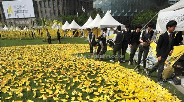 South Korean students put yellow paper ships forming the shape of a heart at a memorial for victims of the 'Sewol' ferry in Seoul on May 7, 2014/AFP