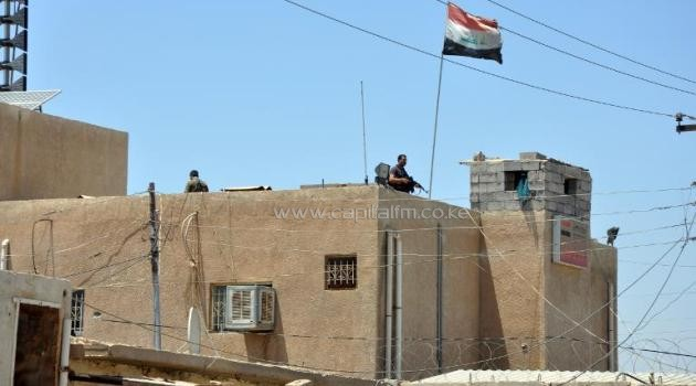 Iraqi security forces guard the Mafraq police station in the Diyala province north of Baghdad on June 18, 2014, which includes a prison where the bodies of 44 prisoners were found the night before/AFP