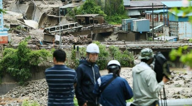 A TV crew films the aftermath of a landslide brought on by Typhoon Neoguri at the Nashizawa river in Nagiso town, Japan's Nagano prefecture on July 10, 2014/AFP