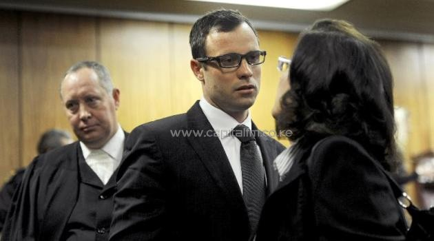 South African Paralympic champion Oscar Pistorius (C) speaks with a member of his legal team ahead of the final arguments of his murder trial at the high court in Pretoria on August 7, 2014/AFP