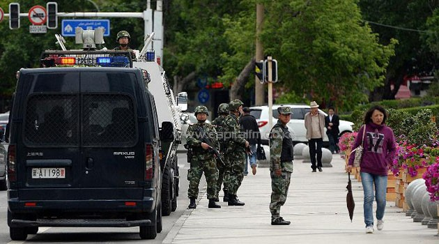 Chinese paramilitary police stand guard along a street in Urumqi, the capital of Xinjiang, on May 23, 2014/AFP